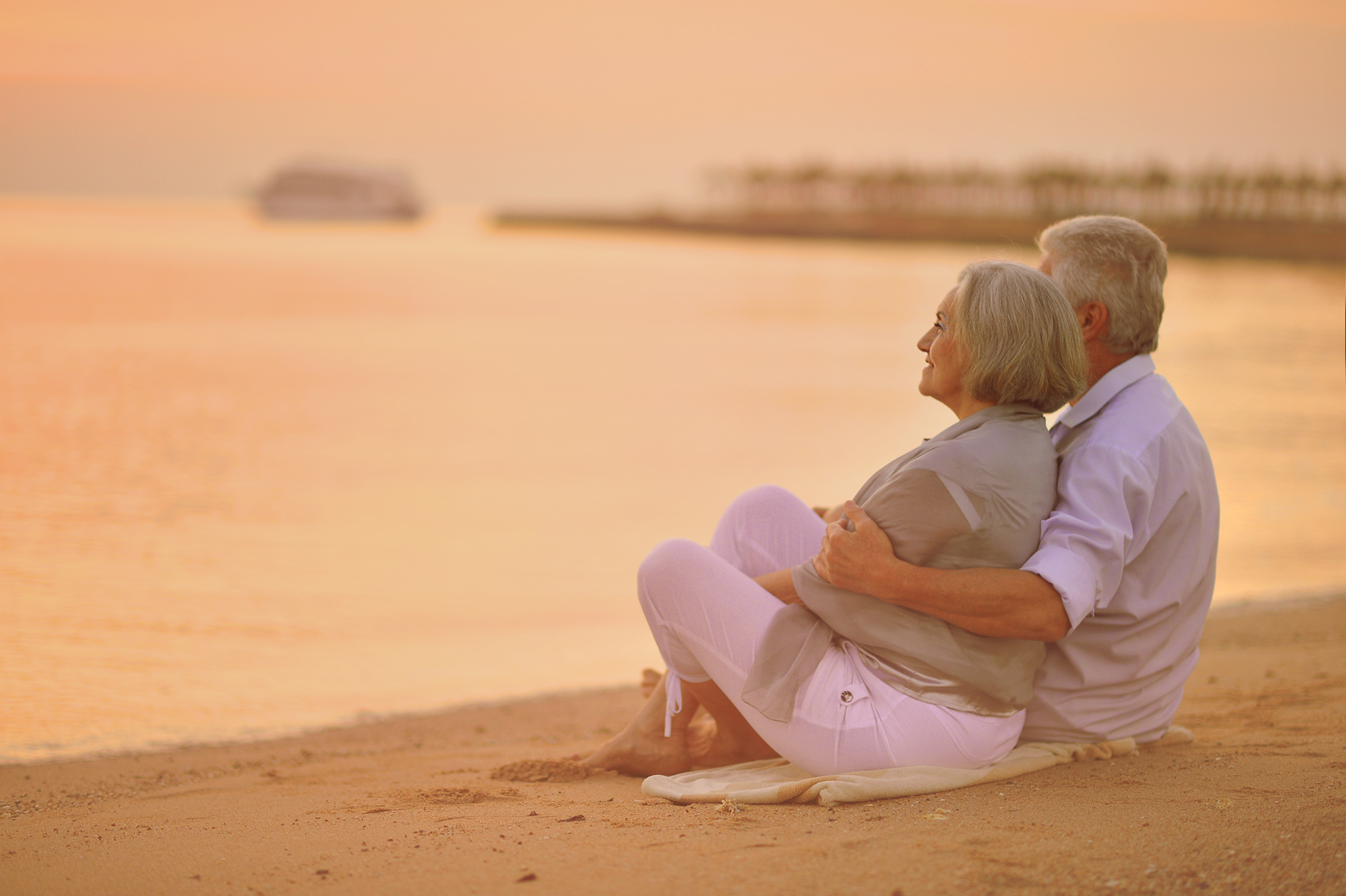 mature couple sitting on the beach